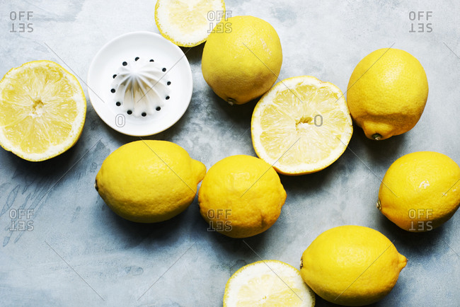 Whole and sliced lemons with citrus squeezer