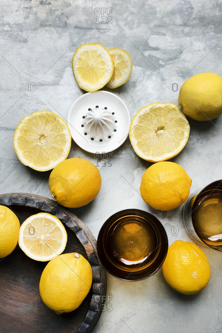 Whole and sliced lemons with citrus squeezer and glasses