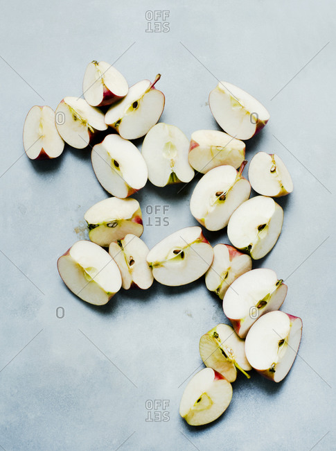 Organic apples cut into fourths on plain background