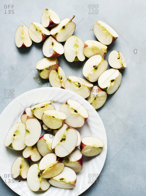 Organic apples cut into fourths on white plate