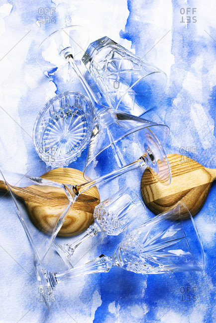 Top view of assorted crystal glasses and wooden spoons arranged on watercolor background