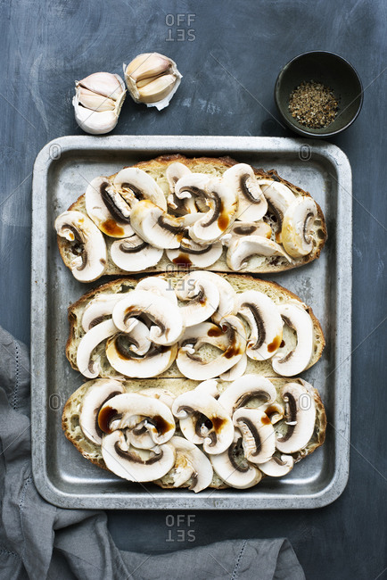 Overhead view of white raw mushrooms on toasts