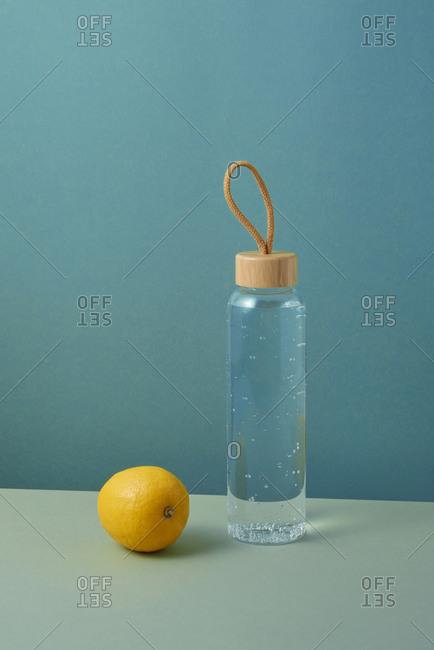 Glass bottle of freshwater with natural lemon.