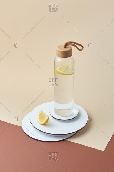 Glass bottle of refreshing lemonade on a white plate.