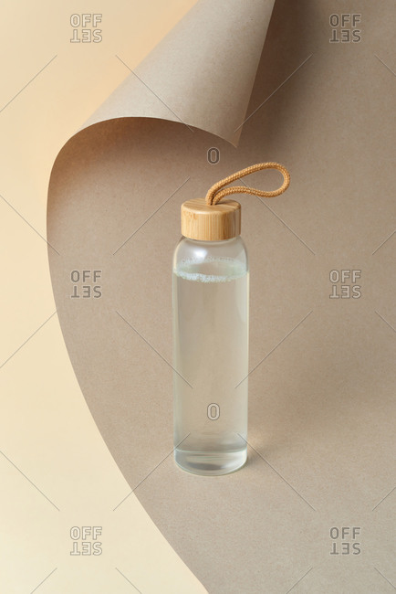 Glass bottle of freshwater on a curved background.