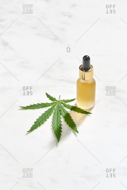 Medical marijuana oil extract and green cannabis leaf.
