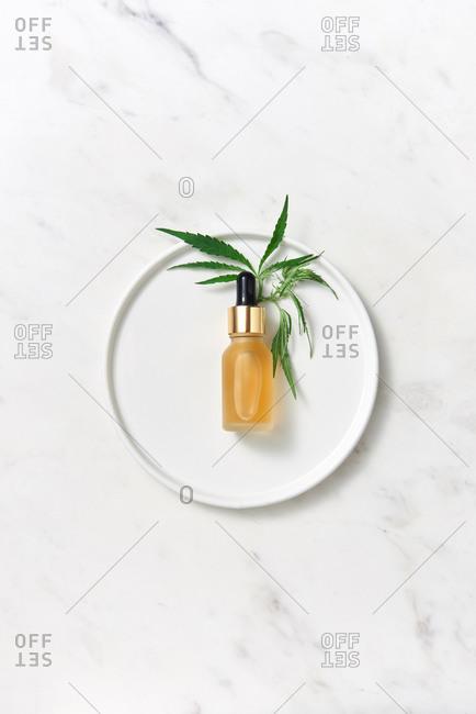 Medical marijuana CBD oil and green leaf on a plate.