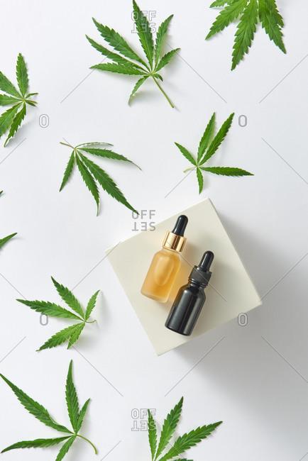 Essential CBD oil in bottles with green cannabis leaf.