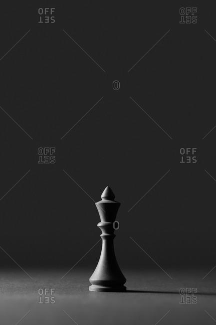 Black chess piece king on a dark background.