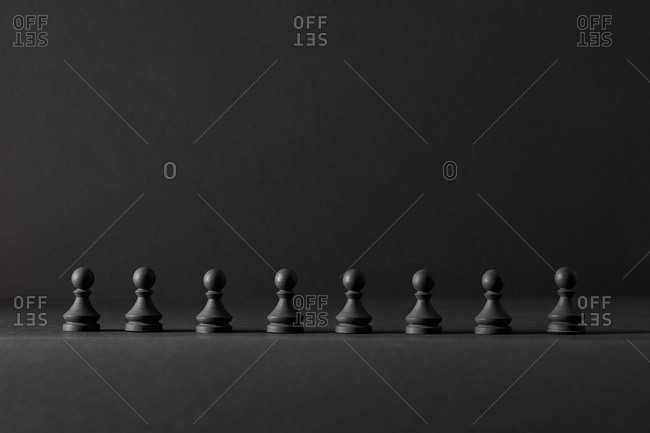 A line from black pawns chess figures.