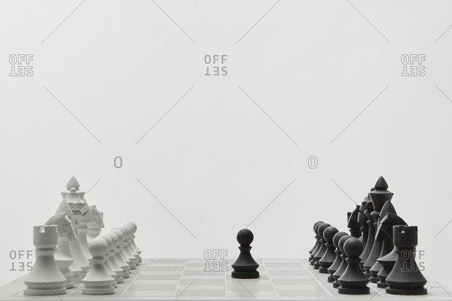 Chessboard with lined up white and black figures.