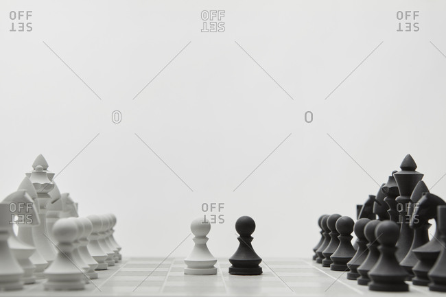 Chess white and black pawns before lined up figures.