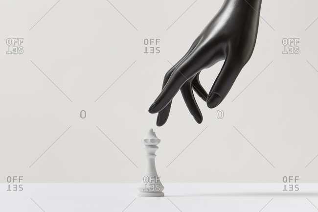 Plastic mannequin hand and white chess queen.