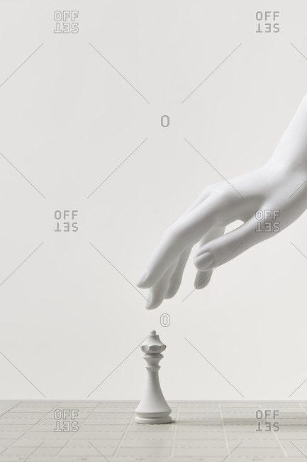 White mannequin hand and chess piece queen.