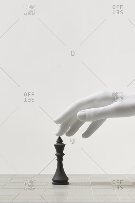 White mannequin hand and black chess piece king.