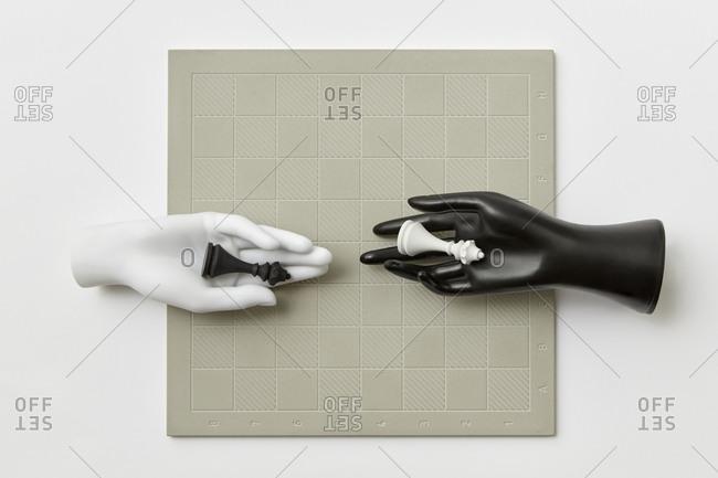 Two plastic mannequin hands with queen figures.