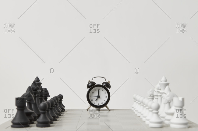 Chessboard before a game with an alarm clock.