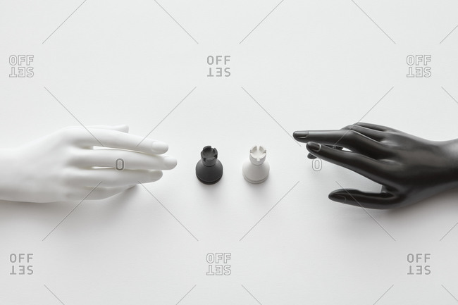 Plastic doll hands with white and black rooks figures.