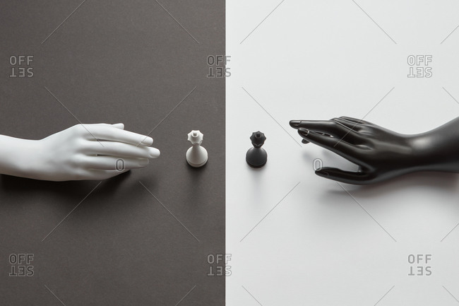 Mannequin hands with white and black queen figures.