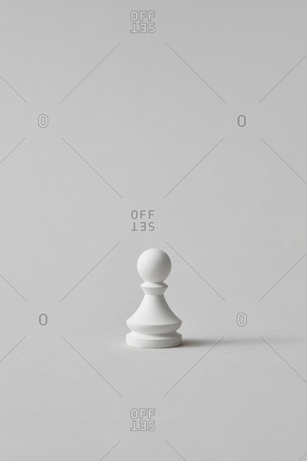 White chess pawn on a grey background.