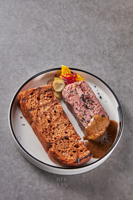 Homemade duck terrine with sauce and rustic bread.