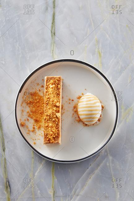 Piece of honey cake with sour cream and sweet ice cream.