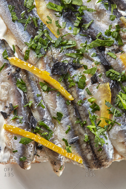 Closeup view snack of fresh anchovies with lemon slices.