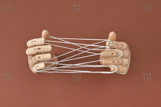 Top view wooden doll's hands play a Cat's cradle game.