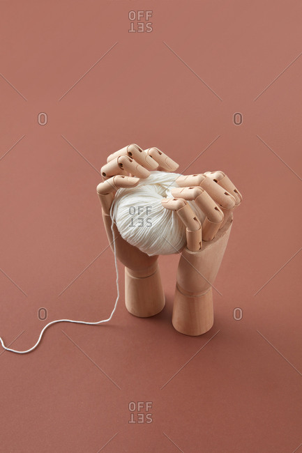 Mannequin's hands hold the ball of white wool yarn.