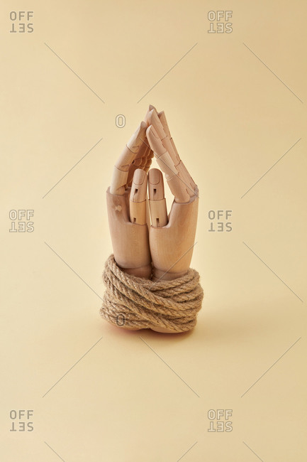 Dummy's hands tied with natural rope.
