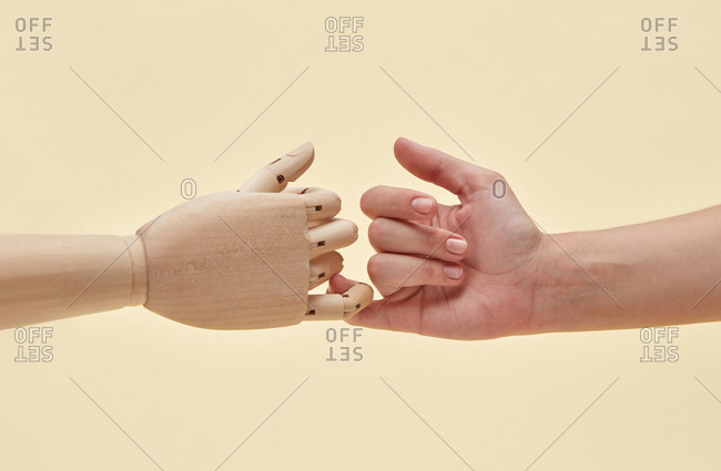 Two little fingers of mannequin and woman are together.
