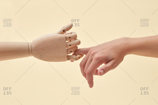 Two little fingers of doll and woman are together.