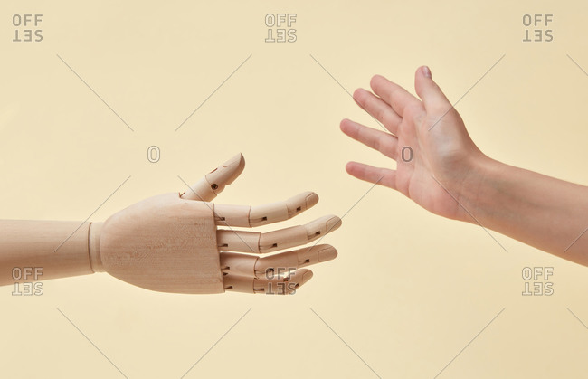 Greeting gesture of female and wooden doll hands