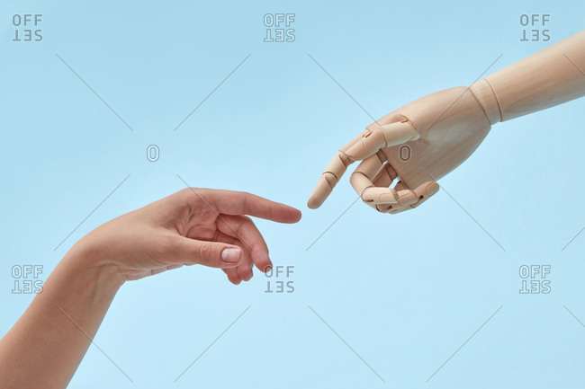 Woman and doll hands with almost touching fingers.
