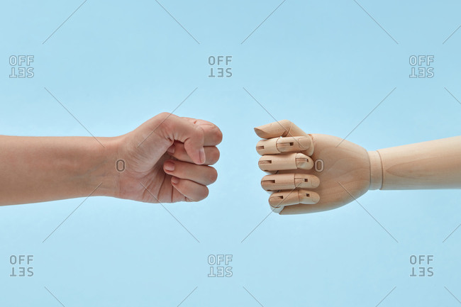 Woman's fist reaching towards a wooden doll's fist.
