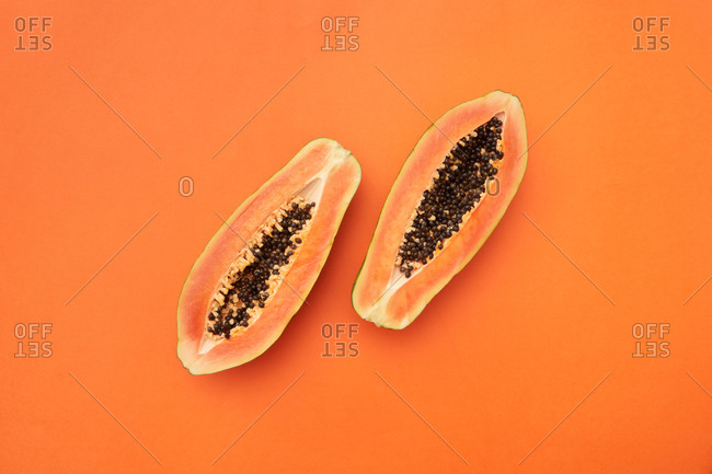Two halves of fresh natural papaya fruit.