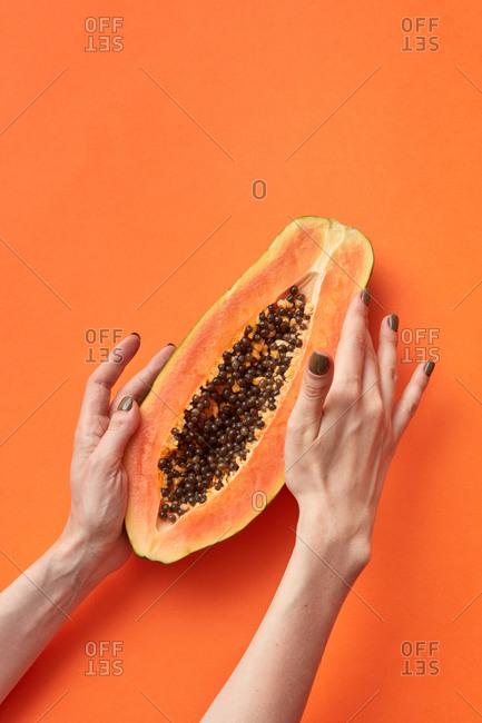 Woman's hands hold half of the ripe natural papaya.
