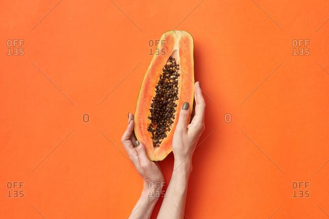 Female hands hold a slice of fresh natural papaya.