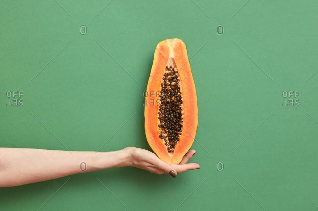 Half of fresh natural papaya fruit in a woman's hand.