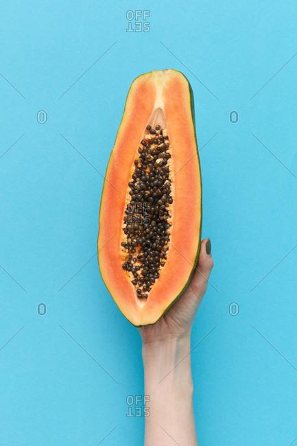 Half of the fresh natural papaya fruit in woman's hand.
