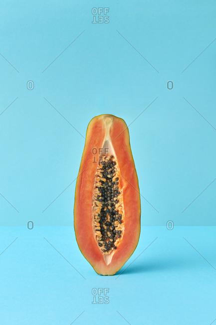 Vertical half of fresh natural papaya fruit.
