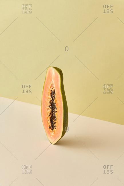 Vertically standing half of the natural papaya fruit.