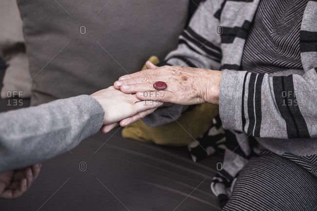A female health worker comforts an elderly woman who is alone