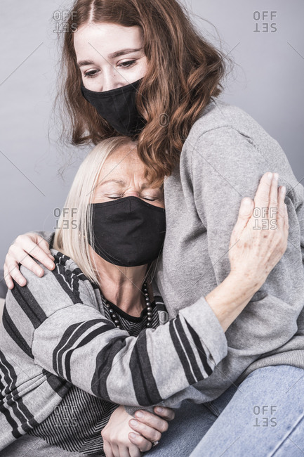 A female health worker comforts an elderly woman who is alone during a pandemic