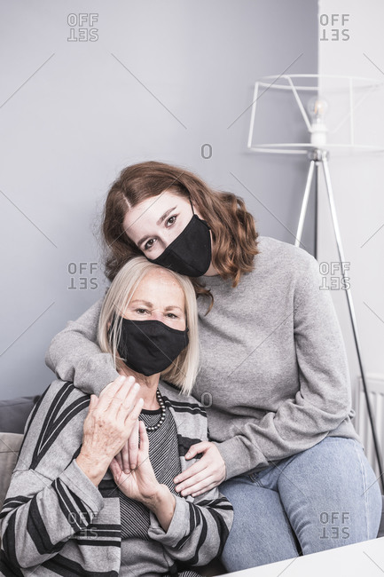 Young female health worker comforting an elderly woman who is alone during a pandemic