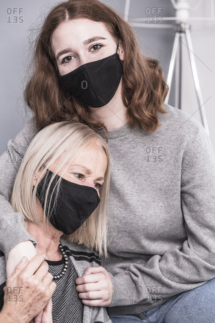 Young female health worker wearing facemask comforting a senior woman who is alone during a pandemic