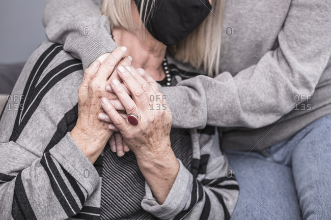 Close up of a health worker holding hands with a senior woman who is alone during a pandemic