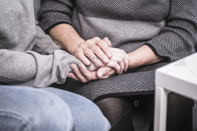 Close up of a young woman holding hands with a senior woman who is alone in her home