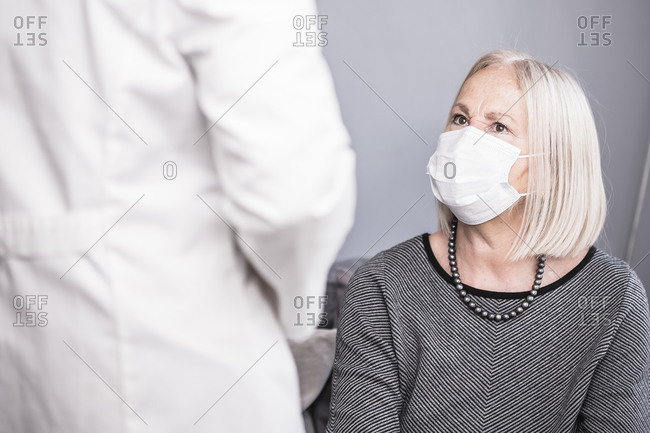 Health worker talking with an elderly woman who is alone during a pandemic