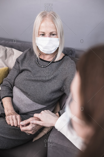 A female health worker holding hands with an elderly woman in her home during the coronavirus